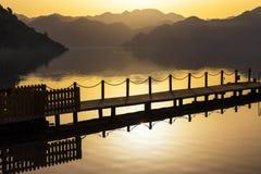 La silueta de la escultura de madera en el mar en la salida del sol Imagen de archivo libre de regalías