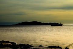 La silueta de la isla en el mar en la puesta del sol Imágenes de archivo libres de regalías