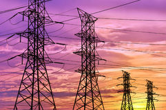 La silueta de la línea eléctrica de alto voltaje se eleva debajo de un cielo colorido de la puesta del sol Imagen de archivo libre de regalías