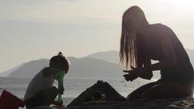 La silueta de la madre y de la pequeña arena del edificio de la hija se escuda en la playa almacen de metraje de vídeo