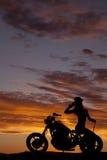 La silueta de la motocicleta de la mujer sienta al revés la mano Foto de archivo libre de regalías