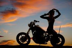 La silueta de la motocicleta de la mujer sienta al revés las manos para arriba Foto de archivo