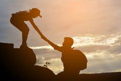 La silueta de la muchacha ayuda a un muchacho en la montaña foto de archivo