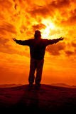 La silueta de la mujer arma encima de extendido para ruega con luz del sol Imagen de archivo