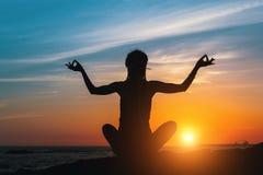 La silueta de la mujer joven de la yoga hace la meditación en la playa del mar Fotografía de archivo