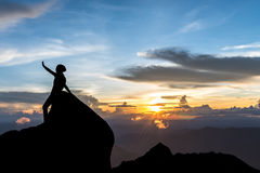 La silueta de la mujer joven en la puesta del sol Imagenes de archivo
