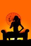 La silueta de la mujer se sienta con el paraguas detrás de la cabeza Imagenes de archivo