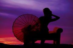 La silueta de la mujer se sienta con el paraguas para echar a un lado Foto de archivo libre de regalías