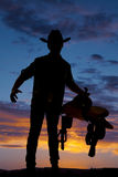 La silueta de la silla de montar de la tenencia del vaquero en la cadera distribuye Fotos de archivo