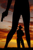 La silueta de las piernas de la mujer con el arma mantiene al vaquero Imágenes de archivo libres de regalías