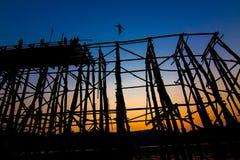 La silueta de los acros viejos del puente del hundimiento del puente del puente de madera Foto de archivo libre de regalías