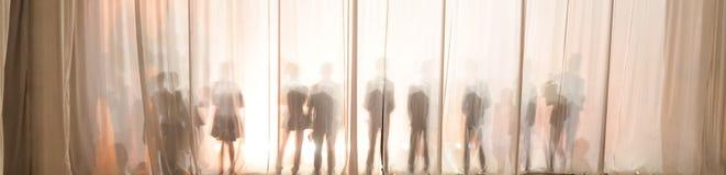 La silueta de los hombres detrás de la cortina en el teatro en etapa, la sombra detrás de las escenas es similar al blanco y al b Imagen de archivo