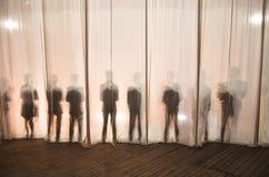 La silueta de los hombres detrás de la cortina en el teatro en etapa, la sombra detrás de las escenas es similar al blanco y al b Imágenes de archivo libres de regalías