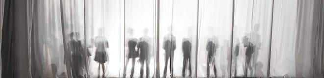La silueta de los hombres detrás de la cortina en el teatro en etapa, la sombra detrás de las escenas es similar al blanco y al b Fotografía de archivo