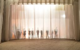 La silueta de los hombres detrás de la cortina en el teatro en etapa, la sombra detrás de las escenas es similar al blanco y al b Imagen de archivo libre de regalías