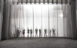 La silueta de los hombres detrás de la cortina en el teatro en etapa, la sombra detrás de las escenas es similar al blanco y al b Fotos de archivo