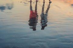 La silueta de los pares que caminaban y que hablaban en la playa con la sombra del descenso reflejó en superficie de la agua de m imágenes de archivo libres de regalías