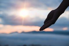 La silueta de la mano que alcanza humana con la palma sube en vagos de la salida del sol fotografía de archivo libre de regalías