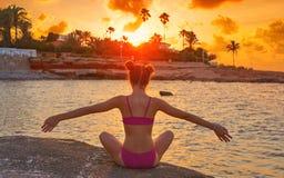 La silueta de la muchacha en los brazos abiertos de la playa se relajó fotografía de archivo libre de regalías