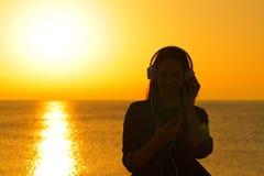 La silueta de la mujer escucha la m?sica en la puesta del sol en la playa imágenes de archivo libres de regalías