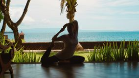 La silueta de la mujer está practicando la meditación en la posición de la yoga, estiramientos, respecto a la playa, hermosa vist almacen de video
