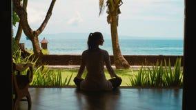 La silueta de la mujer está practicando la meditación de la yoga en la posición de loto respecto a la playa del océano, hermosa v almacen de metraje de vídeo