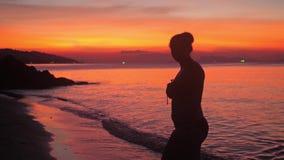 La silueta de la mujer joven en bikini goza el caminar en la playa en la puesta del sol adorable Cámara lenta 3840x2160 metrajes