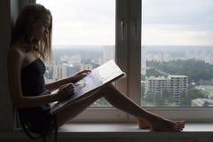 La silueta de la mujer joven está dibujando una pintura de la acuarela en el papel El artista de sexo femenino pinta paisaje del  foto de archivo libre de regalías