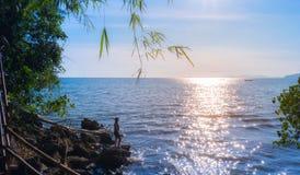 La silueta de la mujer joven goza con puesta del sol en la playa y la sonrisa al sol Imagen de archivo
