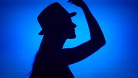 La silueta de la mujer puso el sombrero en la cabeza Cara femenina del ` s en perfil con el tocado en fondo azul almacen de video