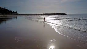 La silueta de la mujer sale del océano que brilla bajo rayos de Sun