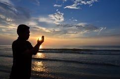 La silueta de musulmanes ruega cerca de la playa Imagen de archivo