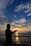 La silueta de musulmanes ruega cerca de la playa Fotografía de archivo