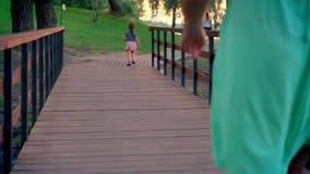 La silueta de la pequeña muchacha está corriendo a lo largo de la trayectoria en parque en el verano, puesta del sol, su madre la almacen de video