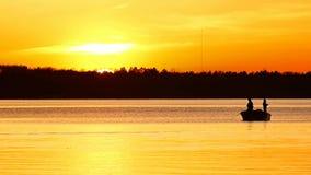 La silueta de la pesca del padre y del hijo en el lago Irving como sol fija almacen de metraje de vídeo