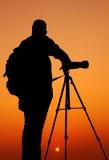 La silueta de Photographer con su trípode Imagen de archivo libre de regalías