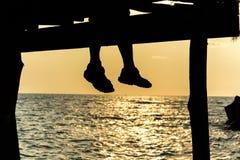 La silueta de pies de pares que se sientan en el embarcadero en la puesta del sol vara Fotos de archivo libres de regalías