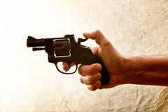La silueta de a sirve la mano con una arma de mano imagen de archivo libre de regalías