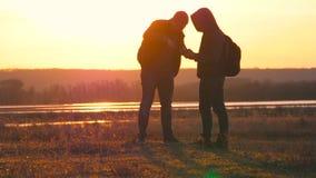 La silueta de la situación de dos mangos en la puesta del sol con las mochilas que expresan energía y felicidad concepto del reco metrajes