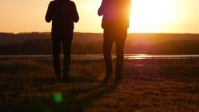 La silueta de la situación de dos mangos en la puesta del sol con las mochilas que expresan energía y felicidad concepto del reco almacen de metraje de vídeo