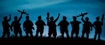 La silueta de soldados militares combina o manda con las armas en Fotografía de archivo