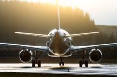 La silueta de un avión iluminado por los contornos del sol pone en contraste en una pista Foto de archivo libre de regalías
