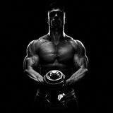 La silueta de un culturista que bombea para arriba muscles con pesa de gimnasia Imagenes de archivo