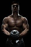 La silueta de un culturista que bombea para arriba muscles con pesa de gimnasia Foto de archivo libre de regalías