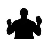 La silueta de un hombre con la obesidad que elige entre la fruta y ayuna Imagen de archivo