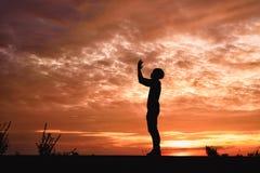 La silueta de un hombre con las manos aumentó en la puesta del sol foto de archivo