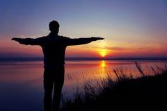 La silueta de un hombre en la puesta del sol Fotos de archivo libres de regalías