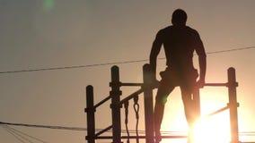 La silueta de un hombre joven para entrenar a su ciudad del gimnasta del cuerpo se divierte almacen de metraje de vídeo