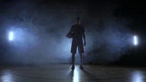 La silueta de un jugador de básquet en un fondo oscuro con humo en la cancha de básquet lanza una bola de la cesta y almacen de metraje de vídeo