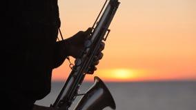 La silueta de un músico que toca el saxofón encendido almacen de video